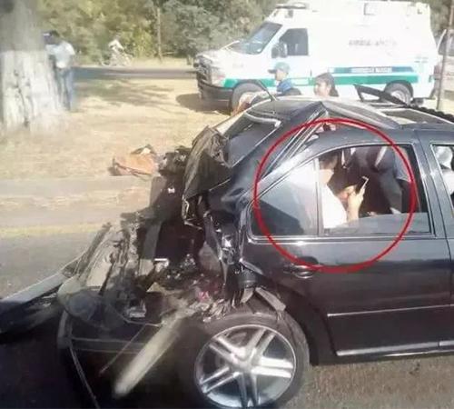 哥们,你的心可真大啊,车都撞成这样了,还能如此专注的玩手机!